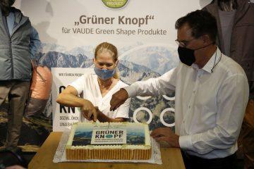 Antje von Dewitz und Gerd Müller schneiden gemeinsam einen Kuchen an