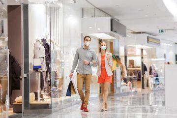 Paar beim Einkaufsbummel mit Masken